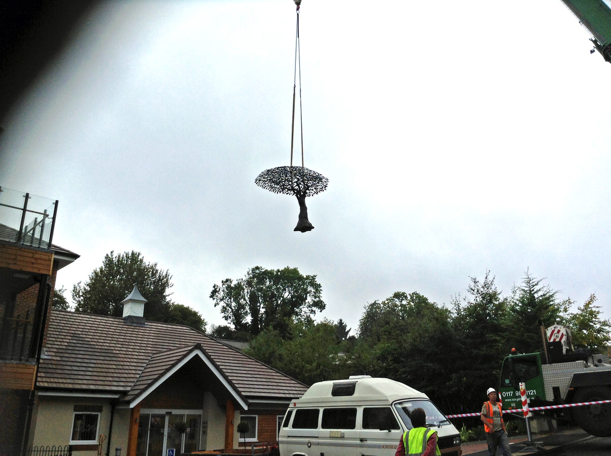 Arbour Metallum monumental tree sculpture commission being lifted over the roof of a hospital by Mark Reed