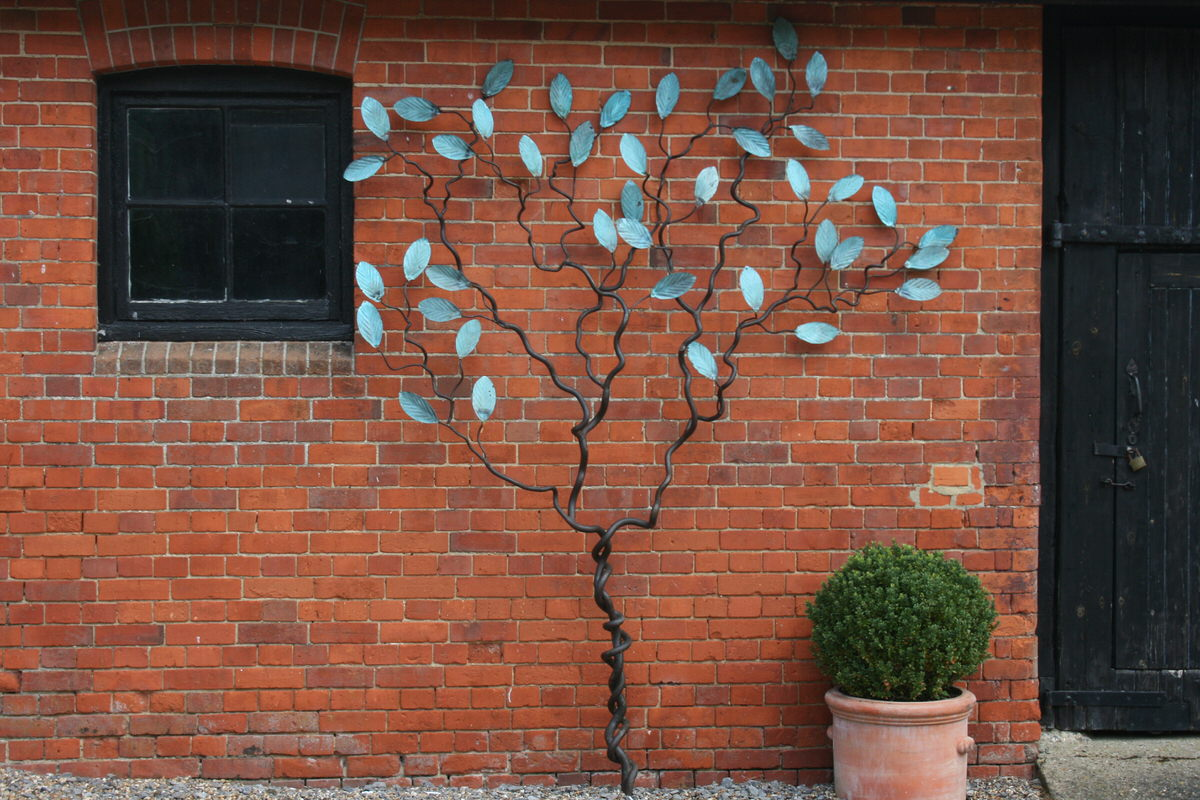 Espalier tree wall climbing sculpture with verdigris leaves by Mark Reed garden sculpture