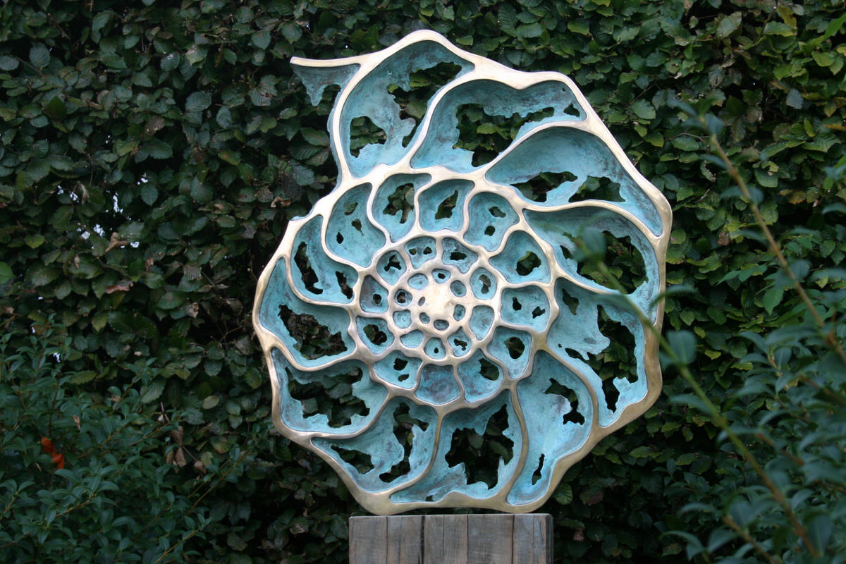 Ammonite slice inside mirror gold plated verdigris bronze in cottage garden sculpture for hotels by Mark Reed