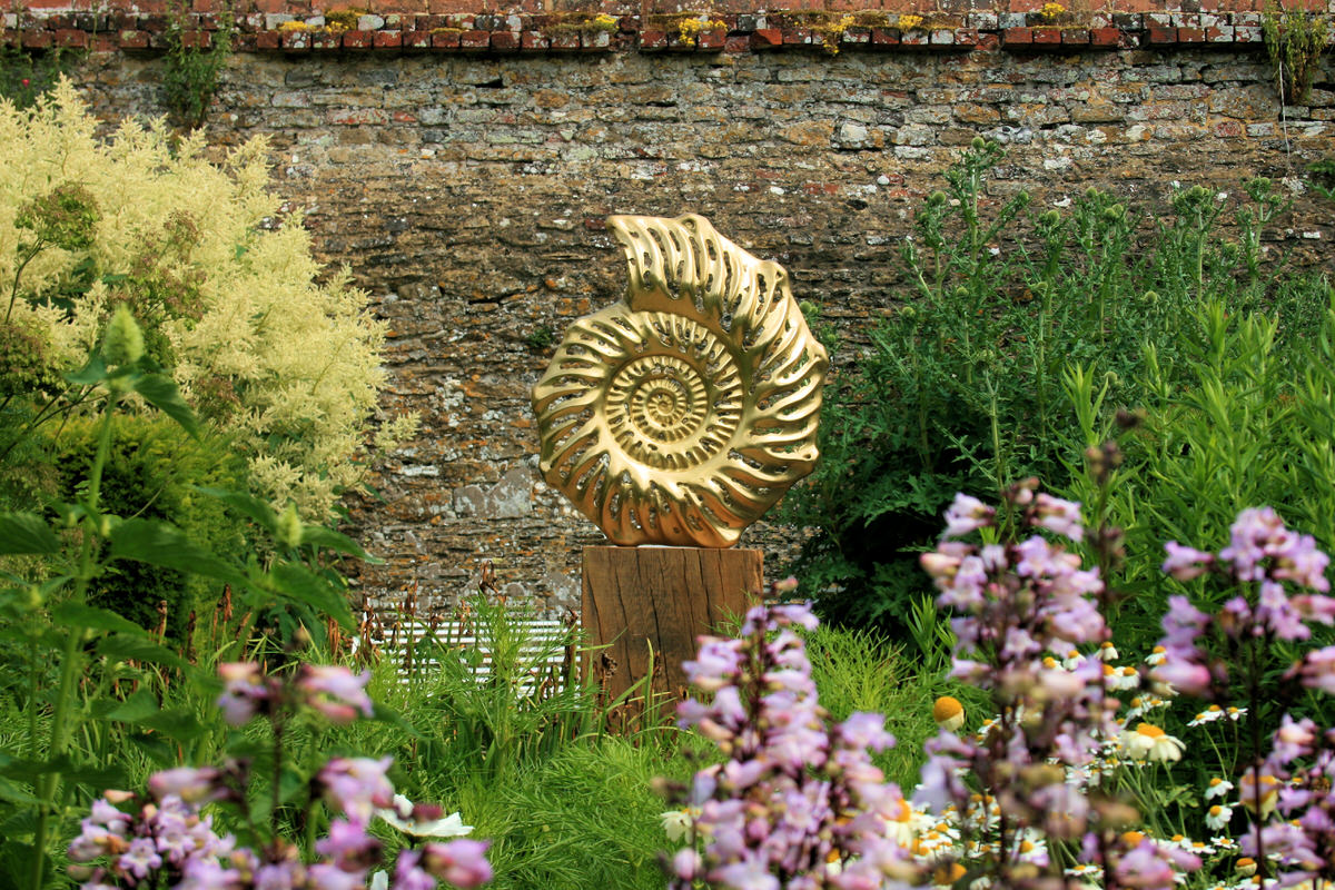 Ammonite slice outside bronze contemporary british sculpture in walled garden landscape by Mark Reed