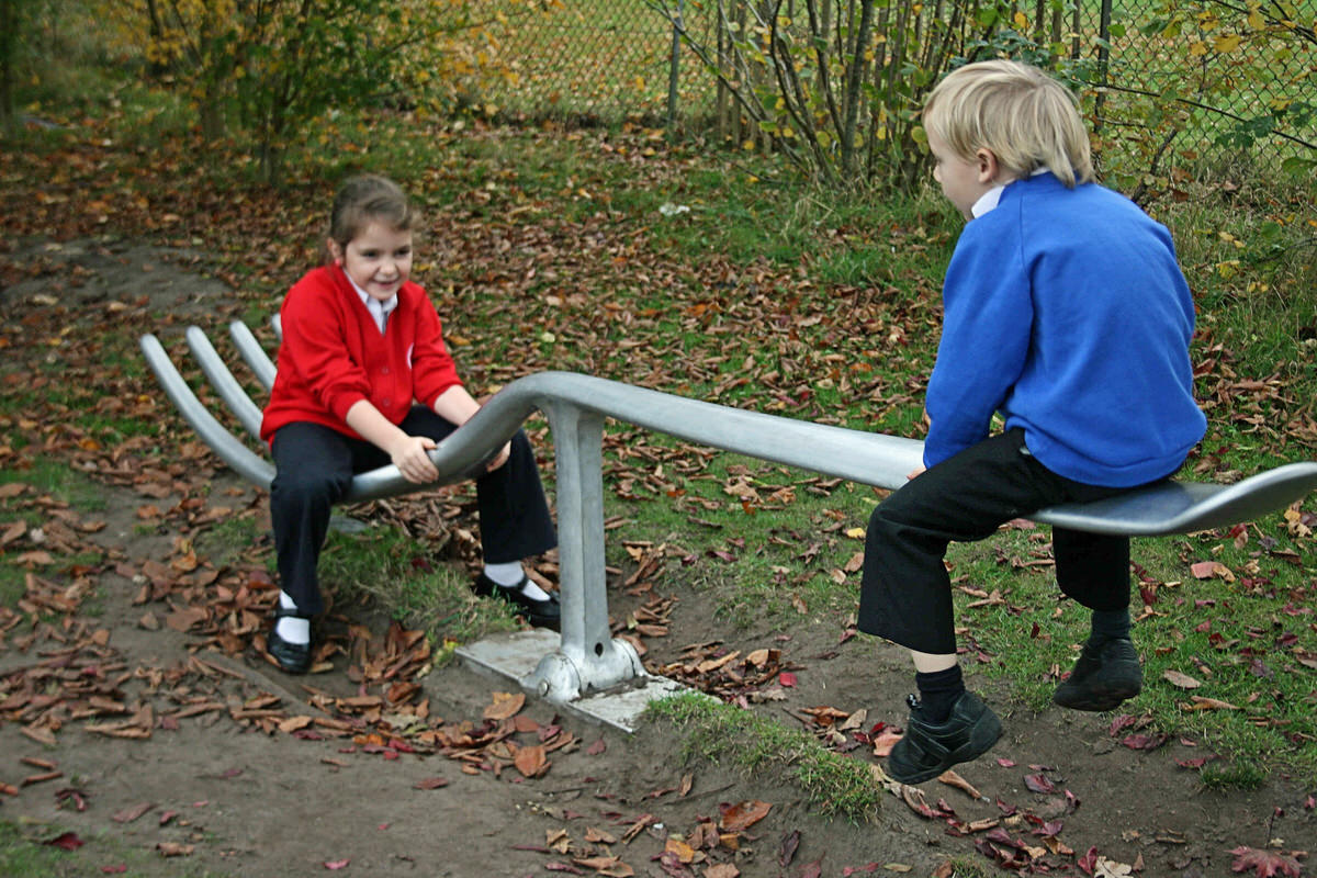 Fork seesaw bespoke recycled alumininum sculpture primary elementary school by British artist sculptor Mark Reed unique garden play apparatus